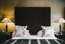 Hospitality PR photograph of a modern bed with decorative pillows with flower accents in an elegant room at Nira Caledonia