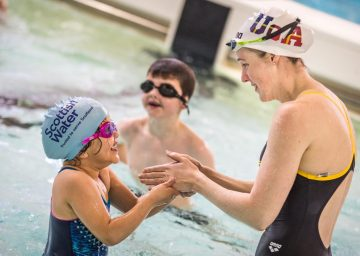 Scottish PR photograph of triple Olympian Hannah Miley teaching children to swim