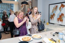 Influencers take pictures of Ruby as she shows guests how to create her singature dish at an event at The Crescent