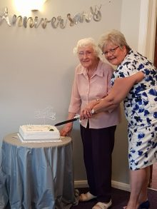 Elizabeth Wilson and Jenny Baird cut the cake to mark Glebe Court's 25th anniversary in a charity PR image