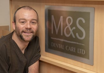 Gregor Muir, dentist and practice owner at M&S Dental Care Ltd crouched in front of a reception sign