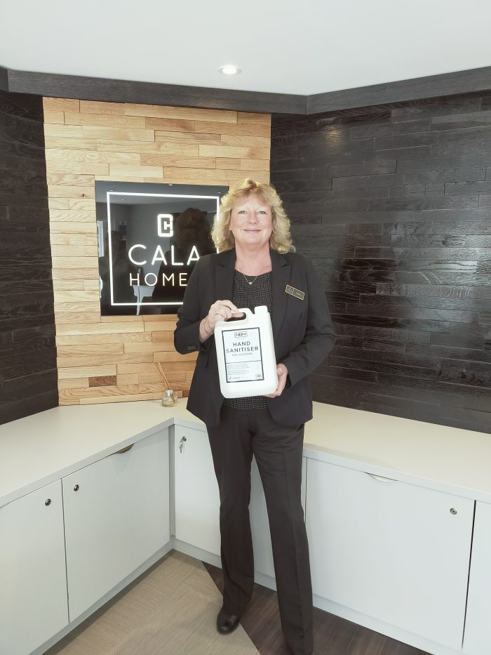 CALA Sales Advisor Amelia Hancock with NB Distillery sanitiser, which has been purchased by the developer as it safely reopens sales offices
