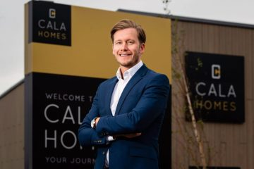 CALA Homes (East) Managing Director Craig Lynes standing in front of CALA totems and branding. Waterfront Plaza, Leith
