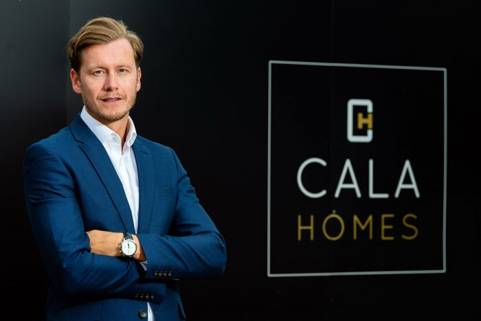 Craig Lynes, MD for CALA Homes (East) standing in front of a board at Waterfront Plaza, Edinburgh