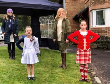 PR Photography of BBC's Jackie Bird with highland dancers Lilly and Lois at Dalriada Grove in care PR story by public relations experts Holyrood PR.