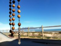 Rosary hanging from an unseen car mirror. Background is a wooden fence separating the car from a span of landscape.