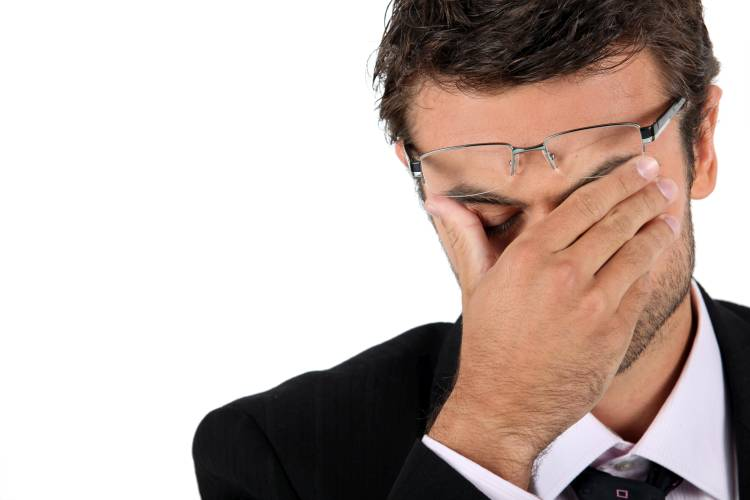 man with glasses having headache
