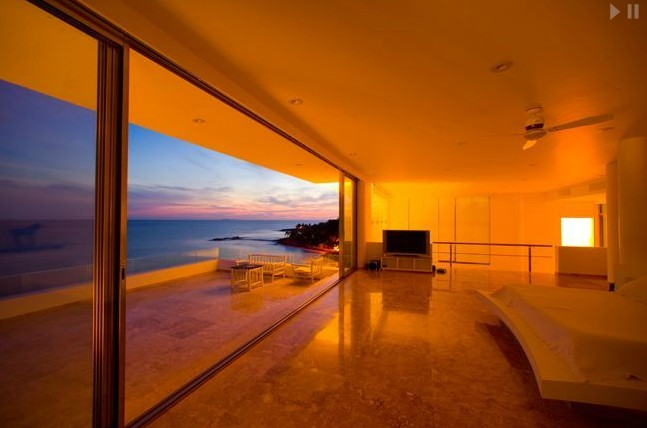The floor-to-ceiling sliding glass doors offer breathtaking views of exquisite, blue seas.