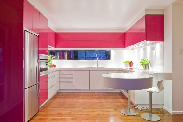 A window backsplash adds extra brightness to this dynamic pink modern kitchen.