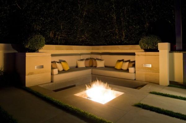 Fogueiras como este são um elemento essencial de qualquer sala de estar ao ar livre.  Este possui um design no chão cercado por built-in de estar.
