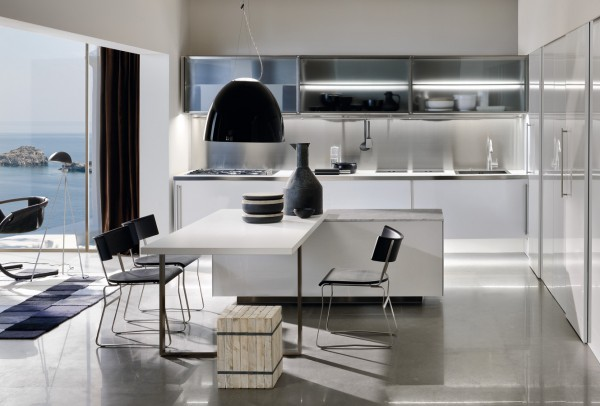 This kitchen space is also multi-functional with the dining table connected to the center island. The white walls and furnishings keep the design clean.