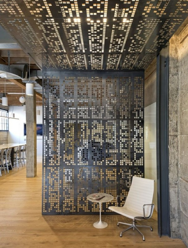 This medal room divider appears almost pixelated, letting it blend easily with the industrial design of this urban loft.