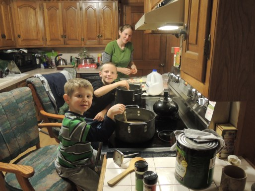 Boys and mom stirring eggnog in kitchen
