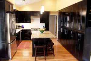black kitchen cabinets with island and wood flooring