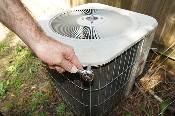 Removing screws from air conditioning condenser unit fan assembly housing