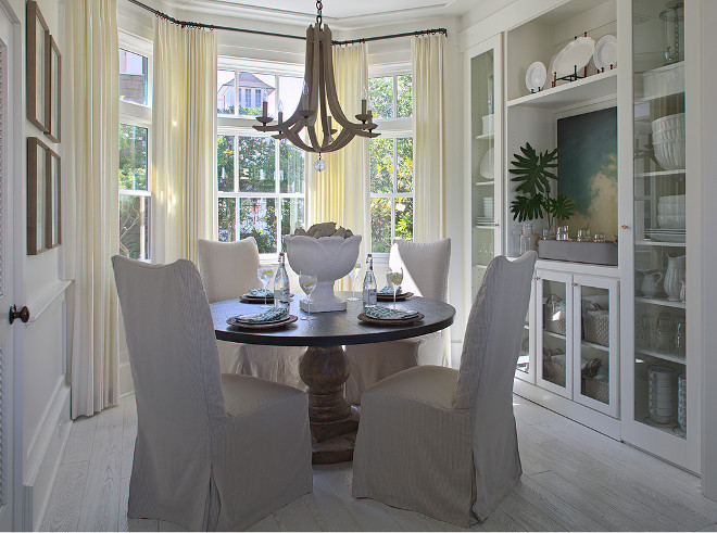 Bay window draperies. Dining room bay window drapery ideas. Beautiful cottage breakfast nook features bay windows dressed in cream curtains filled with round pedestal dining table lined with linen slipper dining chairs illuminated by an Arteriors Manning Chandelier atop white oak floors. Dining room bay windows with floor to ceiling draperies. #Baywindow #Baywindowdraperies #DiningRoomBaywindow #diningroom #Baywindowdarperyideas Urban Grace Interiors