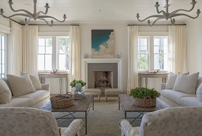 Ivory Living Room. Ivory coastal living room features an ivory beadboard ceiling accented with two light wood chandeliers illuminating a pair of ivory sofas facing each other across from a salvaged wood coffee table surrounded by French doors dressed in floor to ceiling ivory curtains. #LivingRoom #NeutralLivingroom #IvoryLivingroom #Ivoryinteriors #Neutralinteriors Urban Grace Interiors