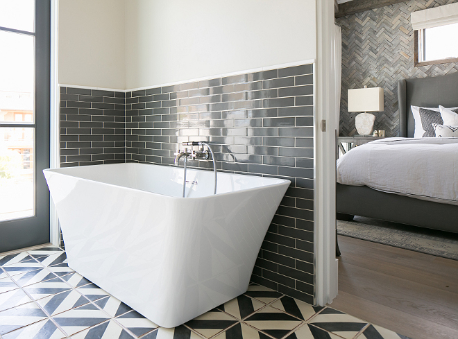 "Bathroom. White and gray master bathroom features upper wall painted in a pale grey and lower wall clad in charcoal gray brick tiles lined with a modern freestanding tub and a wall-mount tub filler atop a white and gray geometric tiled floor. The tub is a Tiffany 59"" Small Soaking tub from Wyndham. #bathroom Patterson Custom Homes"