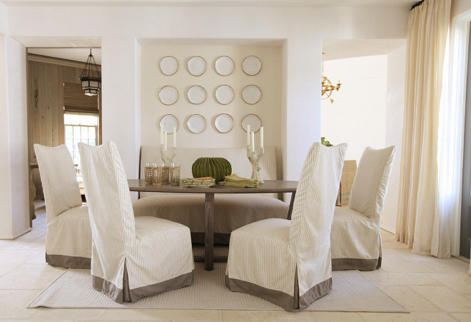 Dining room wall plates Neutral dining room painted in a creamy white paint color and white plates hung on the wall niche. Urban Grace Interiors