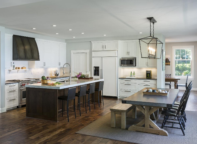 """Transitional kitchen opens to dining room with Darlana Linear Chandelier and Restoration Hardware Zinc top dining table. The perimeter counters are honed Soap Stone (charcoal tones) and the island is Carrera Marble with a mitered 3.5"""" edge. #OpenKitchen #DarlanaLinearChandelier #Zinctable #kitchen Charlie & Co. Design, Ltd. Hagstrom Builders."""