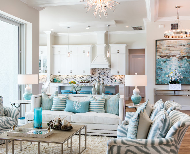 Grey interiors with white cabinets and turquoise decor Beautiful open floor plan home with white kitchen cabinets, grey walls and turquoise decor and accessories. #greywalls #openfloorplan #whitecabinet #turquoise #turquoisedecor Robb & Stucky