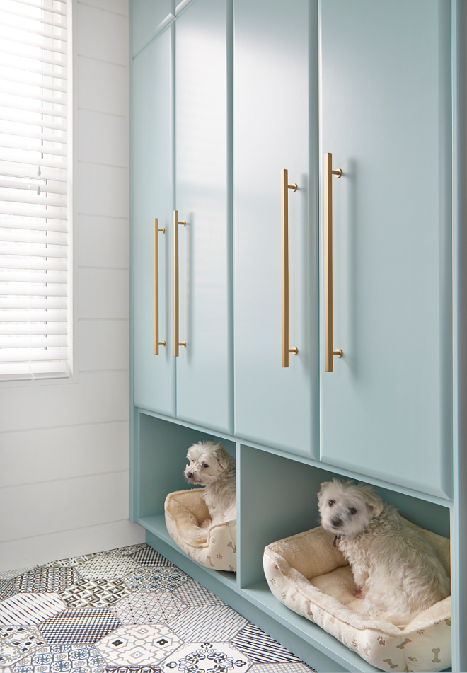 White and black mosaic floor tiles lead to stacked tall turquoise laundry room cabinets in Gossamer Blue by Benjamin Moore accented with brass pulls and fixed above built in dog beds. Flooring is Ceragres St-Barth 8 x 8 hex with laticrete dark grey grout. Walls are finished with a white shiplap trim positioned framing a window. #turquoiselaundryroom #cabinets #GossamerBluebyBenjaminMoore #brasspulls #builtindogbeds Soda Pop Design Inc.