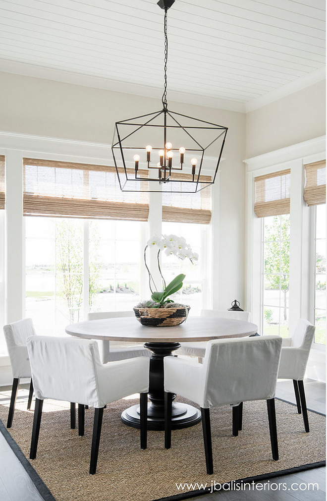 Farmhouse dining room. Farmhouse dining room with a simple design approach and a stricking lighting. Wall paint color is Classic Gray by Benjamin Moore. This #farmhouse dining room features a simple design approach enhanced by a striking lighting. Simply gorgeous! #Lighting is Gabby Decor. #farmhouse #diningroom Judith Balis Interiors