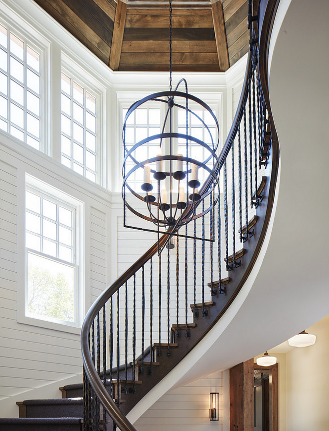 Farmhouse Staircase with white shiplap walls and stained wood shiplap ceiling. Farmhouse-inspired curved staircase with trimmed shiplap walls. white shiplap walls #Farmhouse #Staircase #whiteshiplap #shiplapwalls #shiplap #stainedwoodshiplap #shiplapceiling John Kraemer & Sons