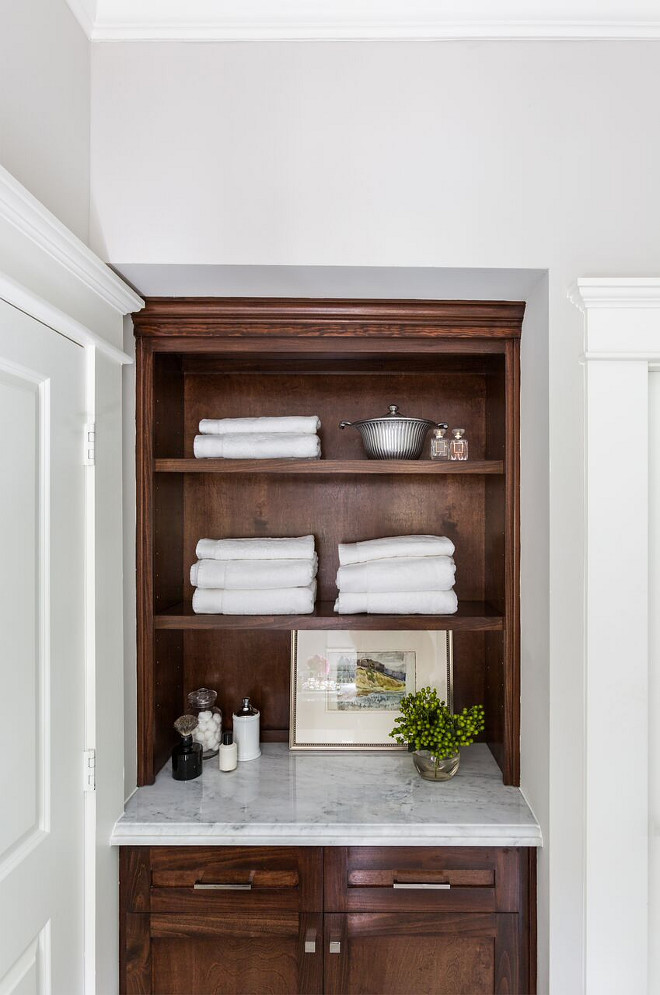 Bathroom linen cabinet. Stained cabinets add warmth to the clean white marble palette. Marie Flanigan Interiors