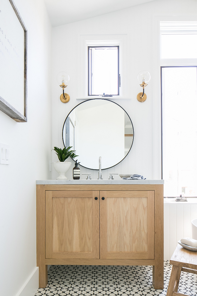 Farmhouse bathroom with black and white cement tile, white oak vanity, round metal mirror and brass glass sconces