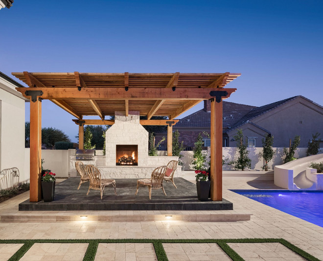 Pergola with black slate tile and stone fireplace. A Finer Touch Construction