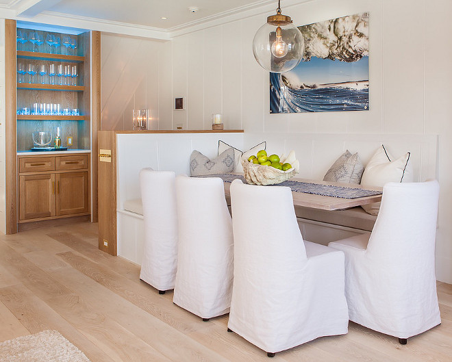 Coastal Dining Room Banquette Ideas Vertical shiplap slipcovered dining chairs coastal wall art glass globe lighting
