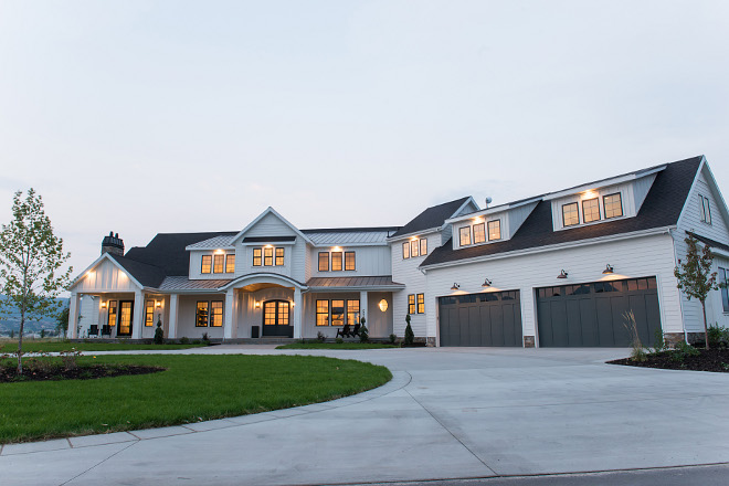 White modern farmhouse exterior with grey garage doors and grey front door