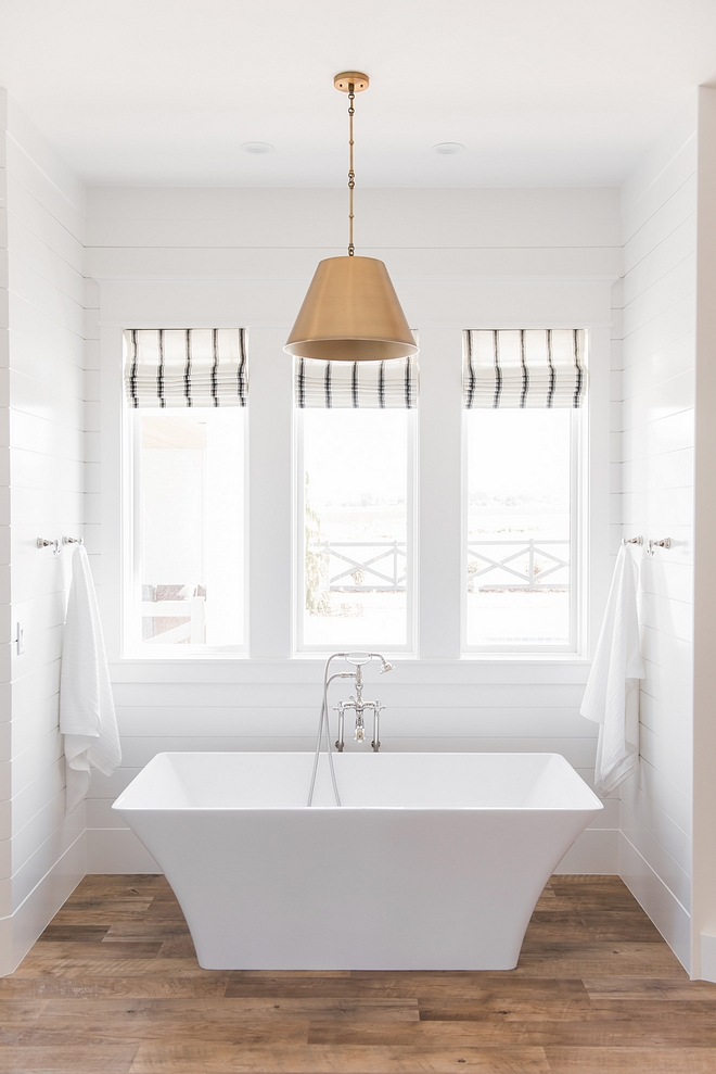 Modern farmhouse bathroom with shiplap freestanding tub, plank vinyl flooring, brass cone pendant and striped back and white roman shades
