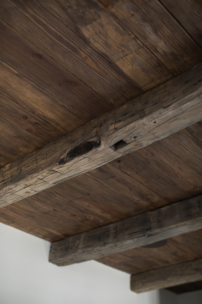 reclaimed barn wood beams over regular cedar planks distressed with nails, chains, and hammers