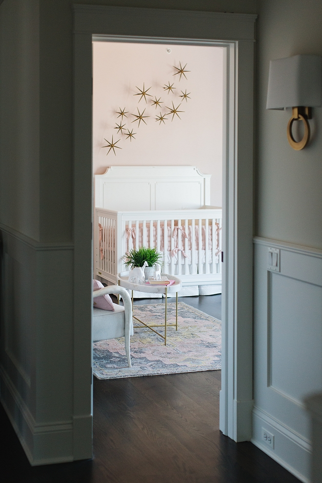 A grey hallway, painted in Benjamin Moore Classic Gray, leads to a blush pink nursery