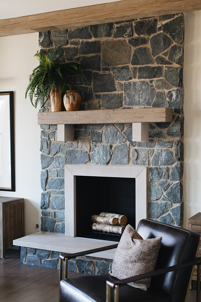 Farmhouse Fireplace The fireplace features a grey natural stone and rustic beam mantel Farmhouse fireplace