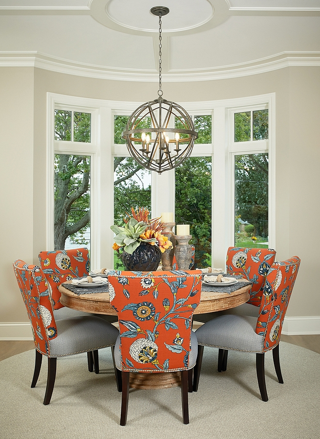 Dining room features a round dining table sisal rug and dining chairs with floral fabric Lighting source on Home Bunch #diningroom