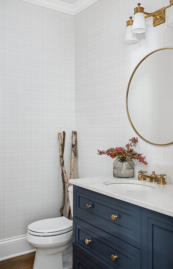 Bathroom with plaid wallpaper Zodiaq in London Sky quartz countertop round brass mirror brass pull hardware and navy blue cabinet