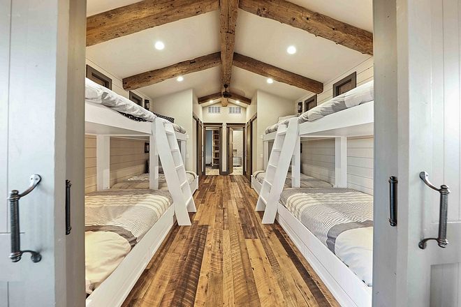 Farmhouse Bunk Room with four bunk beds reclaimed hardwood floors and reclaimed Timber beams #farmhouse #farmhousebunkroom #farmhousebunkbeds #bunkroom #reclaimedhardwoodfloor #reclaimedtimber #timberceiling #reclaimedhardwood #reclaimedwood