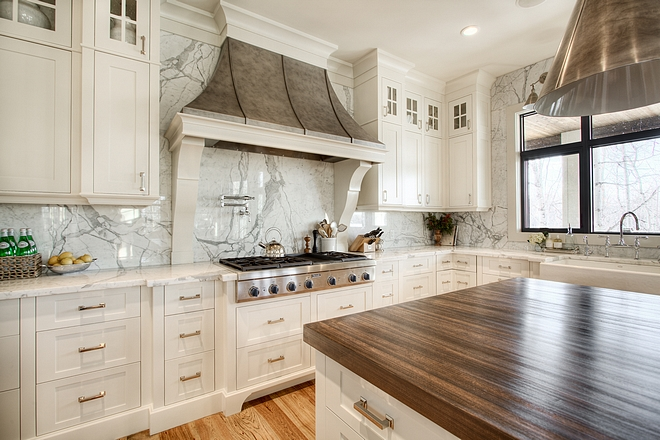 Perimeter countertop and slab backsplash is Statuario marble Kitchen Custom stainless steel hood and cabinetry is accented by the solid slab marble back splash and countertops