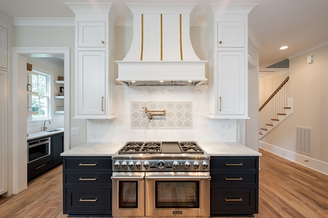 Kitchen features Honed Marble backsplash with custom picture frame above stove