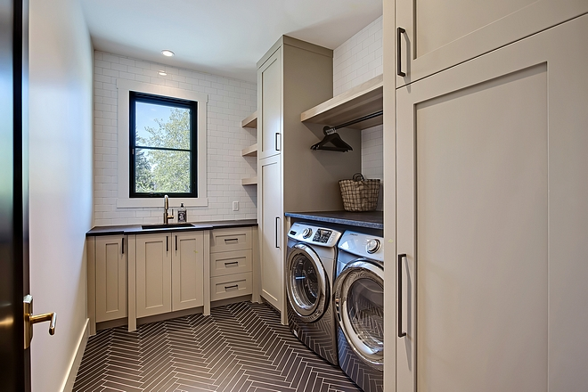 Laundry Room Layout Large laundry room with fixed hickory shelving and lacquered cabinets to the ceiling and hanging rod above the washer and dryer #LaundryRoom #LaundryRoomLayout
