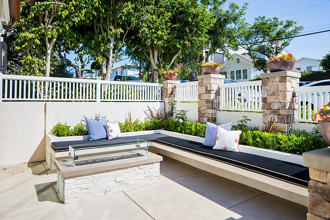 This inviting courtyard features a custom floating bench against flower beds Flooring is acid washed concrete #courtyard #outdoorbench #floatingbench