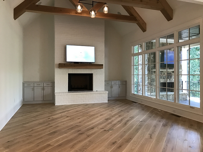 Modern Farmhouse family room features exposed trusses ceiling and a painted brick fireplace #modernfarmhouse #familyroom #exposedtrusses #trussesceiling #trusses #paintedbrickfireplace