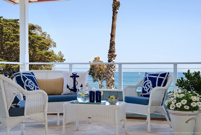 Coastal patio with outdoor white wicker set of sofa, chairs and coffee table Coastal Blue and white outdoor pillows sources on Home Bunch #coastalpatio #whitewicker #outdoorwickerset #outdoorpillows #coastalpillows