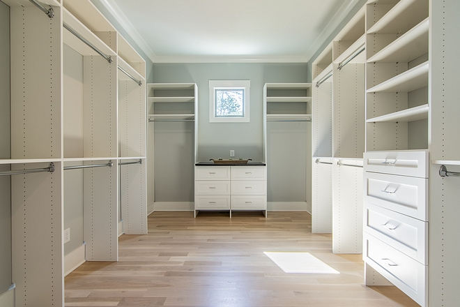 Walk-in closet features White Oak hardwood floors and custom-fit closet system Closet custom-fit closet system #closetsystem #closet #walkincloset