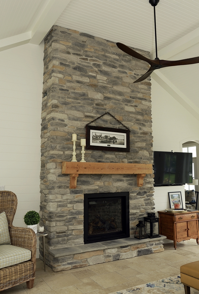 The high vaulted ceilings allowed for a full height traditional heritage stone fireplace. The mantle was salvaged and restored from the original cottage on the property. The white shiplap walls lend nicely to the cottage feel
