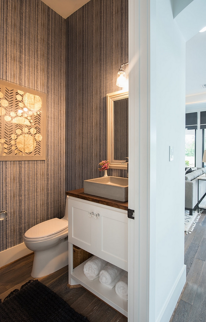 The powder room features a custom vanity with concrete vessel sink and a transitional grasscloth wallpaper #Powderroom #concretevesselsink #vesselsink #Bathroom