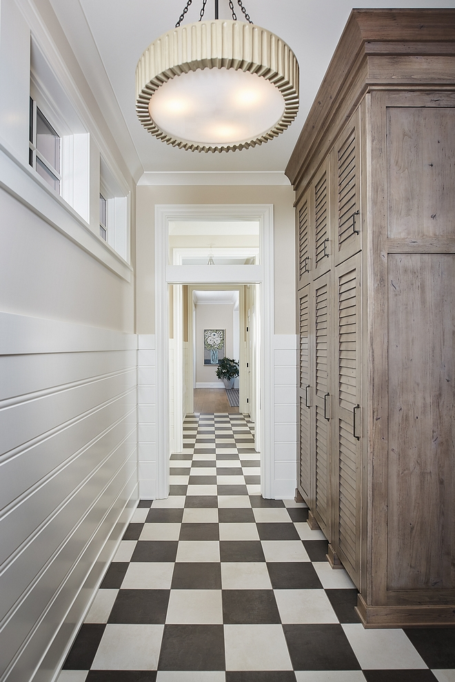 Mudroom featuring a large custom mudroom cabinet with louvered doors, an Arteriors pendant light and classic black and white checkered floor in a matte finish #mudroom #mudroomcabinet #mudroomfloor #mudrooms